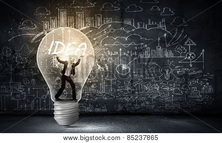 Young businesswoman standing inside of light bulb