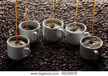 Pouring coffee into five cups on coffee beans