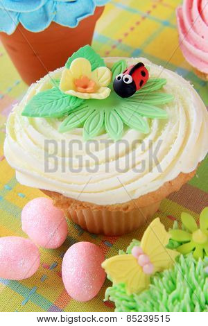 Easter cupcake with a flower and ladybug made of fondant.
