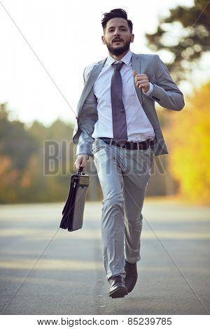 Businessman running in park