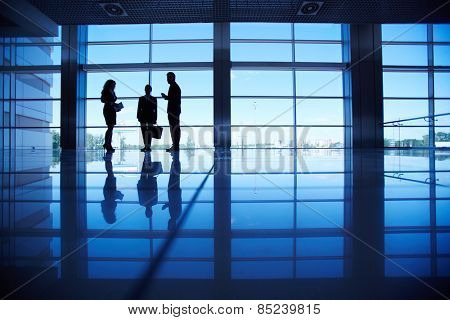 Three business people in dark corridor