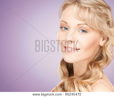 beauty, people, hair care and health concept - beautiful young woman face with long wavy hair over violet background