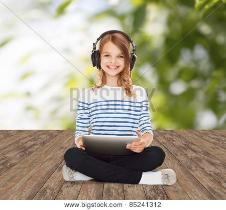music, technology, people and childhood concept - happy girl with headphones and tablet pc computer over greed background