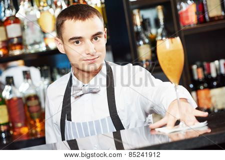 young barman worker at bartender desk serving coctail in restaurant bar