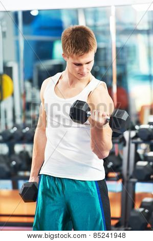 athlete man workout biceps brachii muscles exercises with training dumbbell in fitness gym