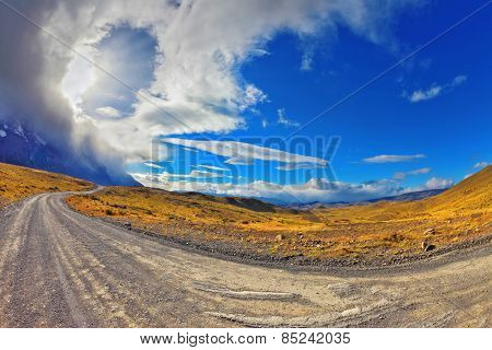 The wind begins. Sunset in the Chilean Patagonia. The gravel road among hills of national park to Torres del Paine