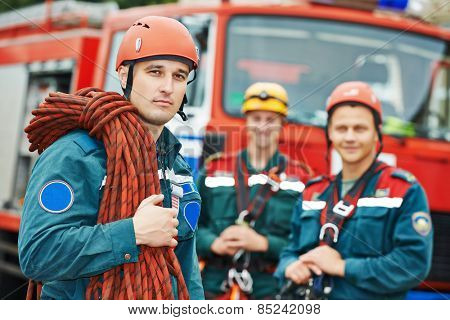 firefighters team in uniform in front of fire engine machine and fireman team