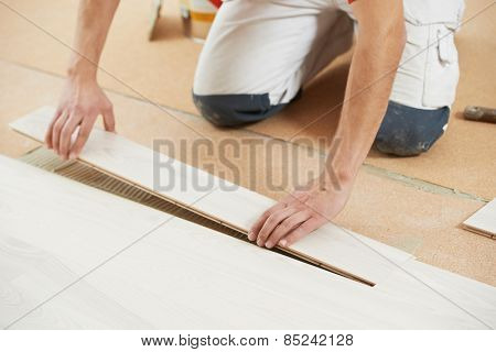 Worker carpenter installing or repair parquet floor on cork flooring layer