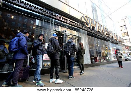 NEW YORK CITY - FEB. 25, 2015:  Pedestrians walk past a Shake Shack restaurant. Shake Shack is a fast casual restaurant chain based in New York City