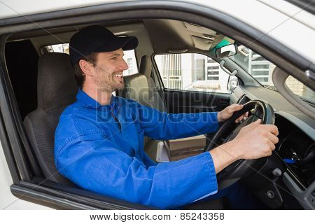 Delivery driver smiling in his van outside the warehouse