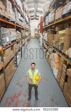 Worker holding hard hat and clipboard in warehouse