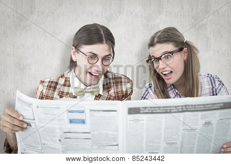 Geeky hipsters reading the newspaper against white background