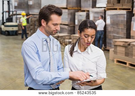 Focused warehouse managers working together in a large warehouse
