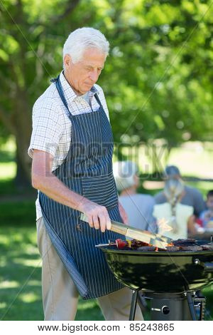 Concentrate grandfather doing barbecue on a sunny day