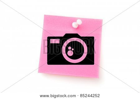 Camera against pink adhesive note with pushpin