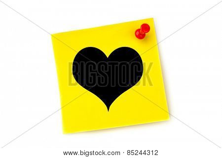 Heart against yellow pinned adhesive note