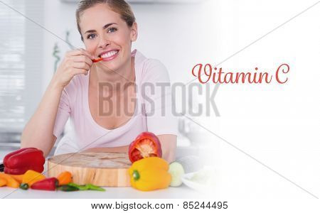 The word vitamin c against cheerful woman eating vegetables