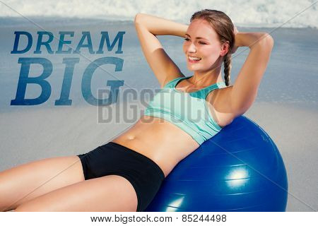 Fit woman lying on exercise ball at the beach doing sit ups against dream big
