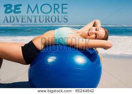 Fit woman lying on exercise ball at the beach stretching against be more generous