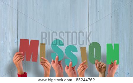 Hands holding up mission against wooden planks