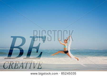 Fit woman jumping gracefully on the beach with scarf against be creative