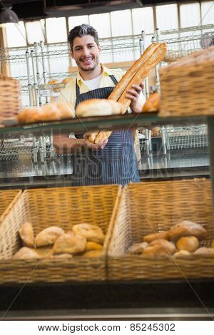 Smiling waiter holding two baguettes at the bakery