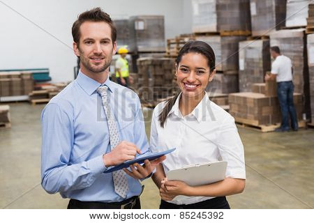Smiling warehouse managers working together in a large warehouse