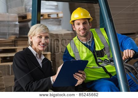 Forklift driver and manager smiling at camera in a large warehouse