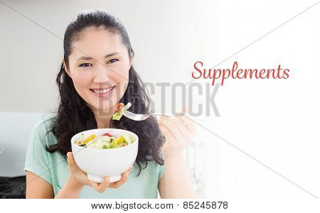 The word supplements against smiling young woman with a bowl of salad in kitchen