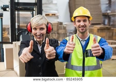 Warehouse worker and his manager giving thumbs up in a large warehouse