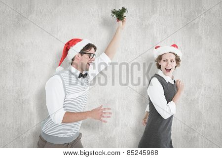 Geeky hipster running away from a man with mistletoe against white background