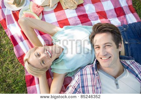 Happy couple lying together at the park on a sunny day