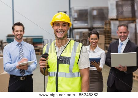 Worker standing with scanner in front of his colleagues in a large warehouse