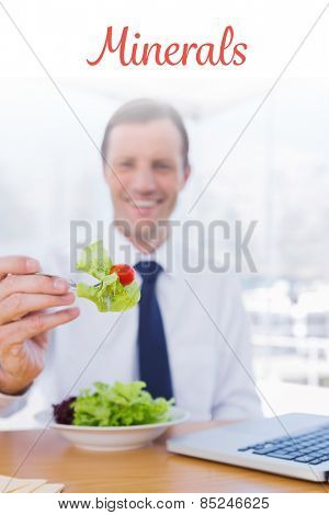 The word minerals against businessman eating a salad