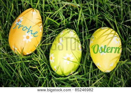 frohe ostern against three easter eggs nestled in the grass