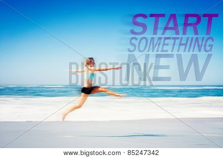 Fit woman jumping gracefully on the beach against start something new