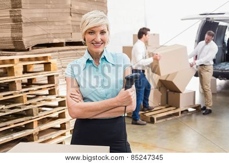 Warehouse manager holding scanner with arms crossed in a large warehouse