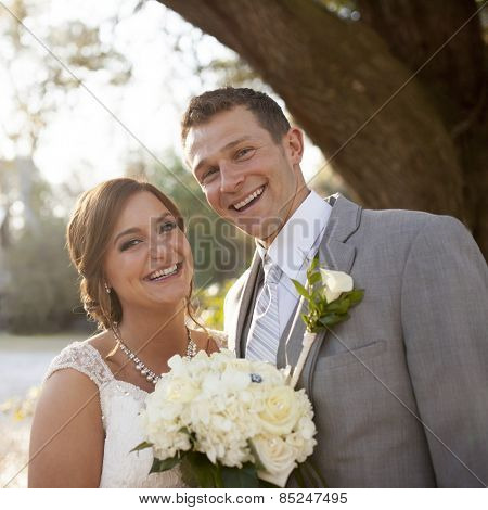 Happy newly married couple outdoors in sunlight