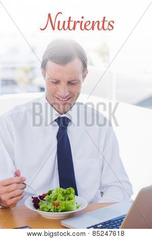 The word nutrients against smiling businessman eating a salad on his desk