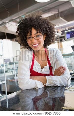 Pretty waitress with glasses leaning on counter at the bakery
