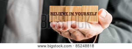 Close Up Conceptual Businessman Showing Wooden Blocks With Believe In Yourself Message In Front Of T