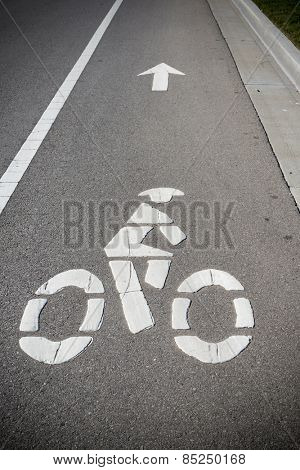 A bike lane or bikeway symbol on asphalt roadway