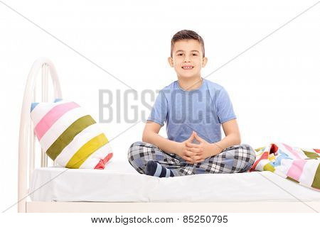 Cute little boy in pajamas sitting on a bed isolated on white background