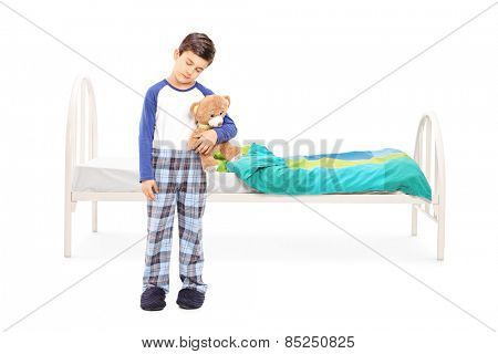 Full length portrait of a sleepy boy standing in front of a bed isolated on white background