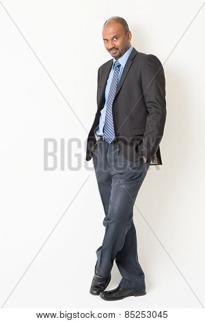Full length cool Indian businessman in formal suit looking at camera, on plain background.