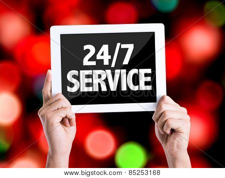 Tablet pc with text 24/7 Service with bokeh background