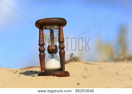 Hourglass in sandy desert in sunny day