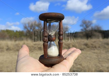 Hourglass on man palm against forest background
