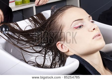 Young woman in hairstyle salon, hair care and healthy hair concept