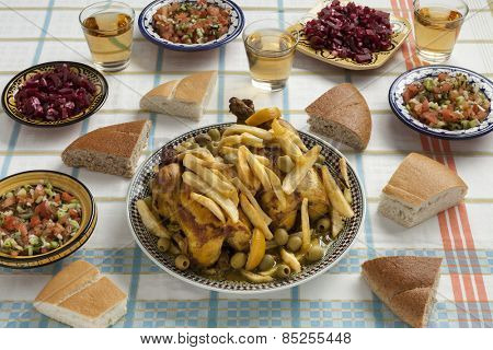 Traditional moroccan stuffed chicken meal with french fries, olives,,preserved lemon,bread and salads on the table
